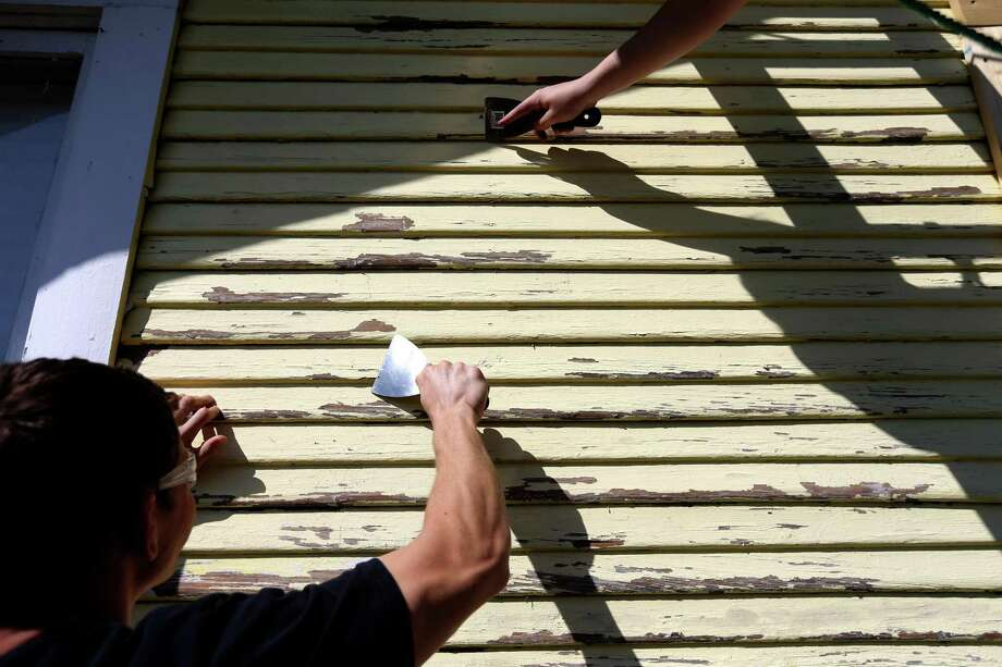 Spencer Smith, 17, and Andrew Kovach, 17, juniors at Houston Christian High School, along with 150 other students, spend their day of service painting a home in the Independence Heights neighborhood, part of a program hosted by Rebuilding Together Houston Wednesday, March 2, 2016, in Houston, Texas. The students painted five houses along the 200 block of E. 31 1/2 St. Rebuilding Together Houston provides free repair and renovation for elderly low-income, disabled and service-veteran homeowners in need. ( Gary Coronado / Houston Chronicle ) Photo: Gary Coronado, Staff / Houston Chronicle / © 2015 Houston Chronicle