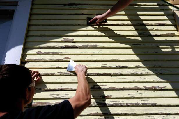 Spencer Smith, 17, and Andrew Kovach, 17, juniors at Houston Christian High School, along with 150 other students, spend their day of service painting a home in the Independence Heights neighborhood, part of a program hosted by Rebuilding Together Houston Wednesday, March 2, 2016, in Houston, Texas. The students painted five houses along the 200 block of E. 31 1/2 St. Rebuilding Together Houston provides free repair and renovation for elderly low-income, disabled and service-veteran homeowners in need. ( Gary Coronado / Houston Chronicle )