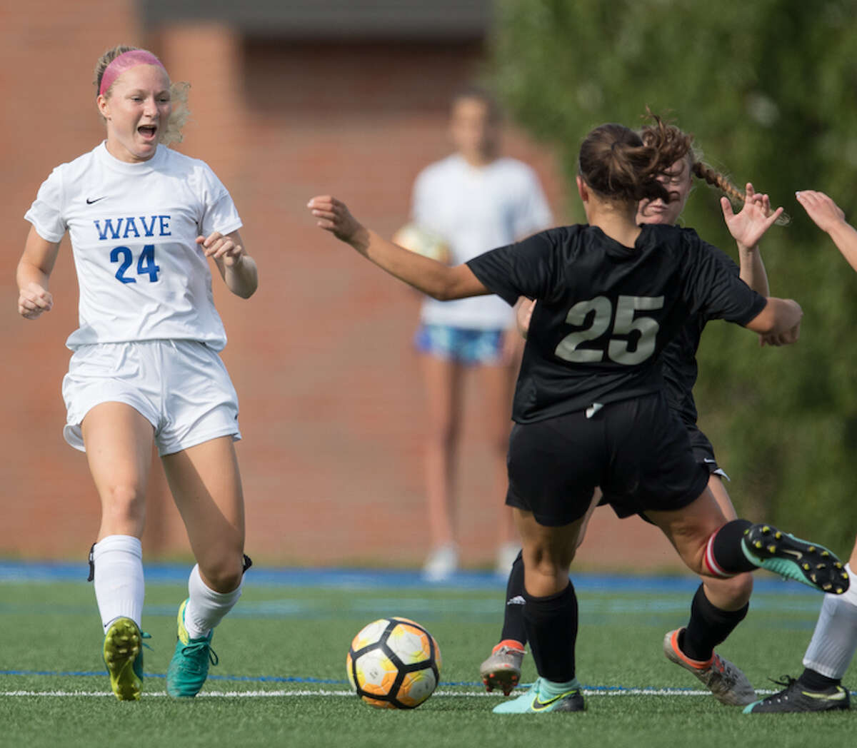 Eva Finn (left) makes herself known to the opposition at midfield. Courtesy Darien Athletic Foundation