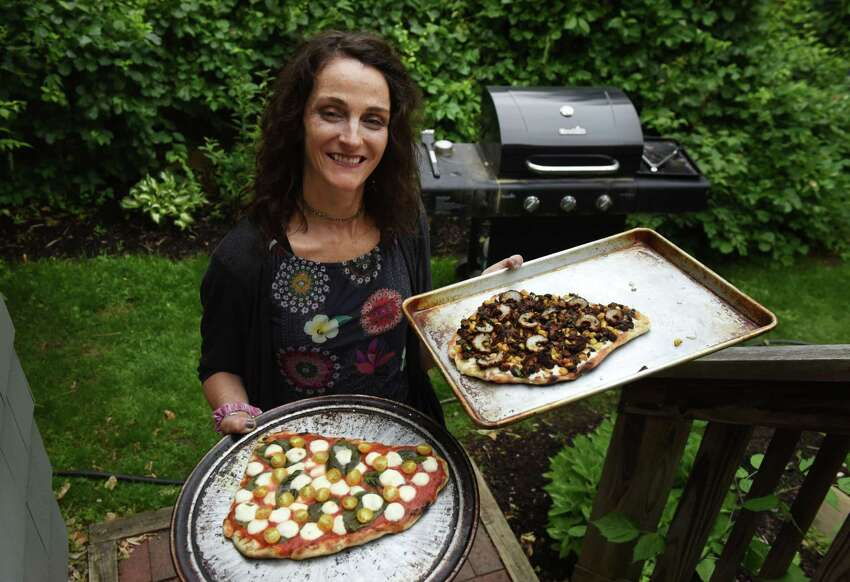 Caroline Barrett holds a Margherita and vegetable pizza on Thursday, June 13, 2019, in Delmar, N.Y. The pizza was cooked on a grill. (Will Waldron/Times Union)