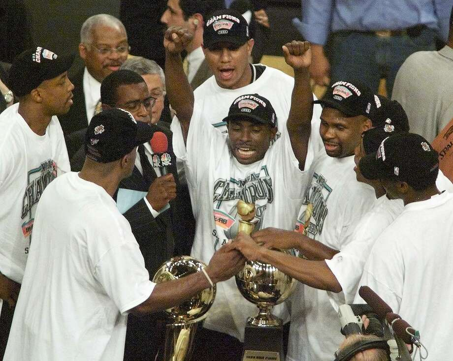 Avery Johnson, center, of the San Antonio Spurs and the rest of team gathers around the championship trophy June 25, 1999, after the Spurs won Game 5 of the NBA Finals against the New York Knicks at Madison Square Garden in New York.  The Spurs won the game 78-77 to win the series 4-1. Photo: Timothy A. CLARY | AFP, Getty Images