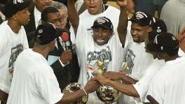 Avery Johnson (C) of the San Antonio Spurs and the rest of team gathers around the championship trophy 25 June, 1999, after the Spurs won game five of the NBA Finals against the New York Knicks at Madison Square Garden in New York.  The Spurs won the game 78-77 to win the series 4-1.