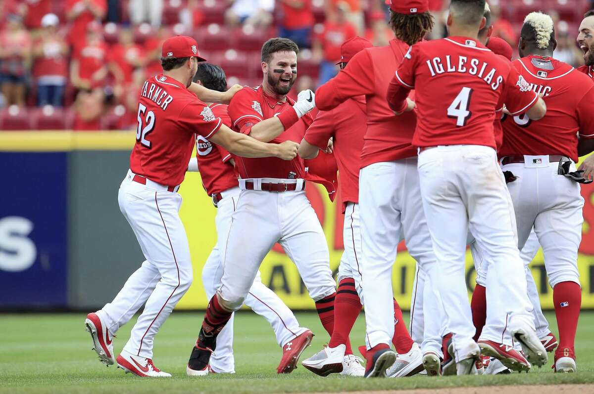 Cincinnati's Jesse Winker, center, is mobbed by teammates after delivering a ninth-inning walk-off single to complete the Reds' three-game sweep of the Astros.