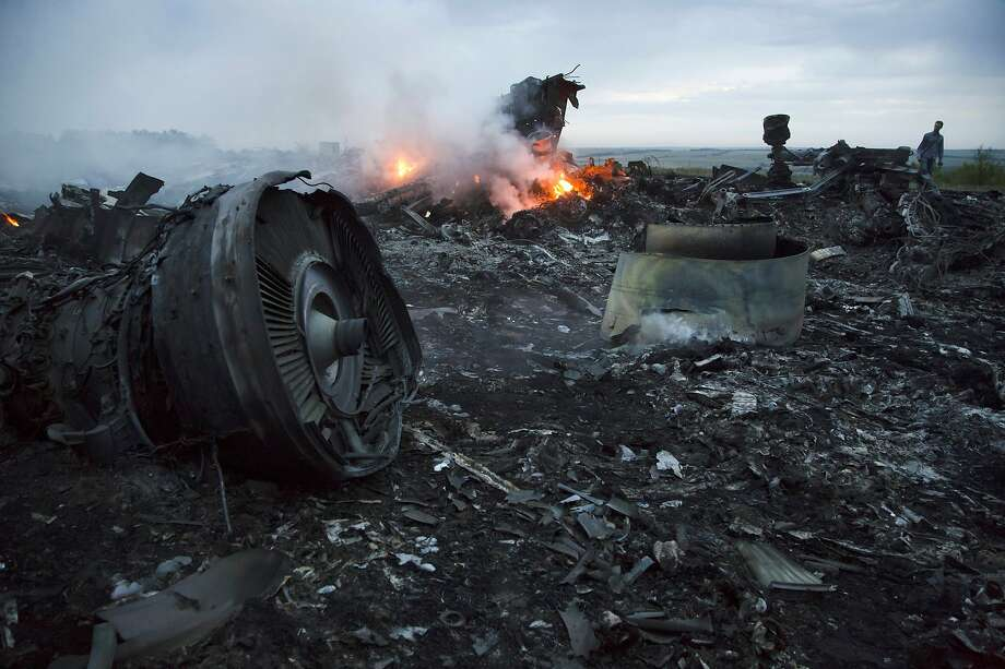 Debris from Malaysia Airlines Flight 17 burns near the village of Hrabove, Ukraine, in 2014. Four suspects face trial in March in the deaths of all 298 aboard after the plan was shot down. Photo: Dmitry Lovetsky / Associated Press 2014