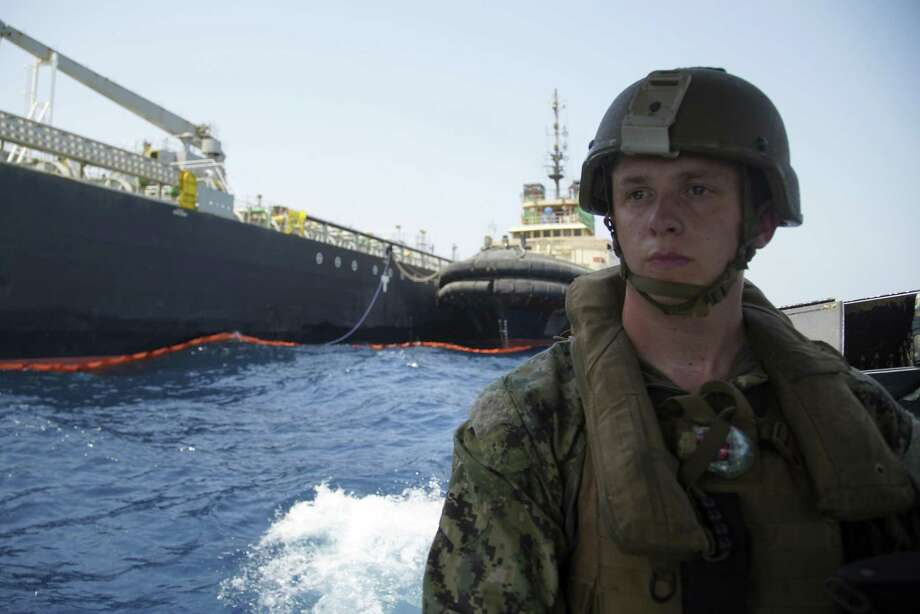 """The damaged Panama-flagged, Japanese owned oil tanker Kokuka Courageous, that the U.S. Navy says was damaged by a limpet mine, is seen behind a U.S. sailor, during a trip organized by the Navy for journalists, off Fujairah, United Arab Emirates, Wednesday, June 19, 2019. The limpet mines used to attack the oil tanker near the Strait of Hormuz bore """"a striking resemblance"""" to similar mines displayed by Iran, a U.S. Navy explosives expert said Wednesday. Iran has denied being involved. (AP Photo/Fay Abuelgasim) Photo: Fay Abuelgasim, STF / Associated Press / Copyright 2019 The Associated Press. All rights reserved."""