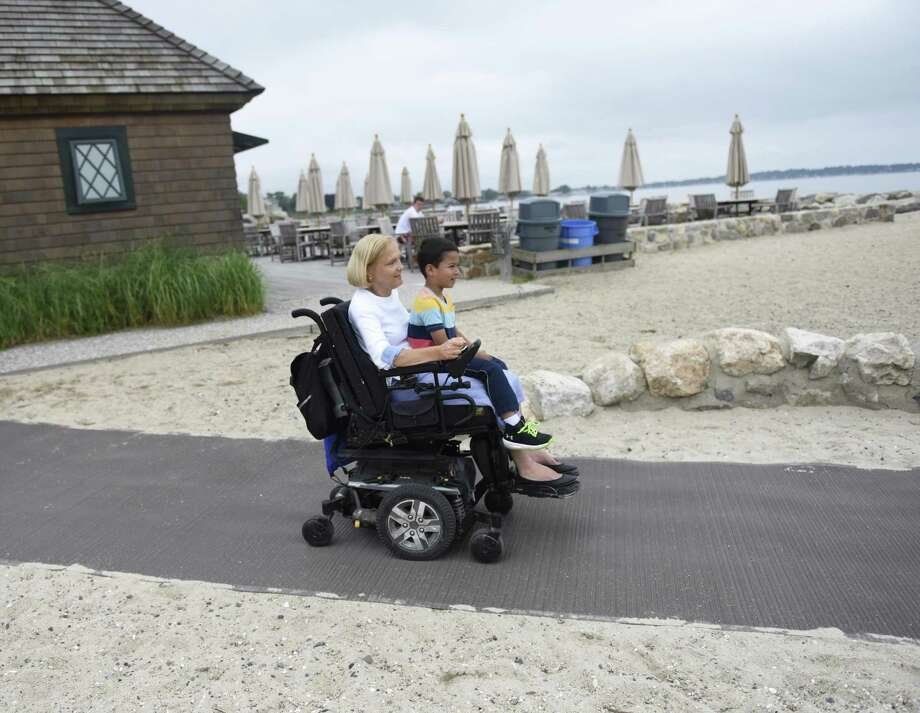 Greenwich residents Anne Hotchkiss and Angelo Arista, 5, use the new ADA accessible ramp on the Greenwich Point Park beach in Old Greenwich on Wednesday. Photo: Tyler Sizemore / Hearst Connecticut Media / Greenwich Time
