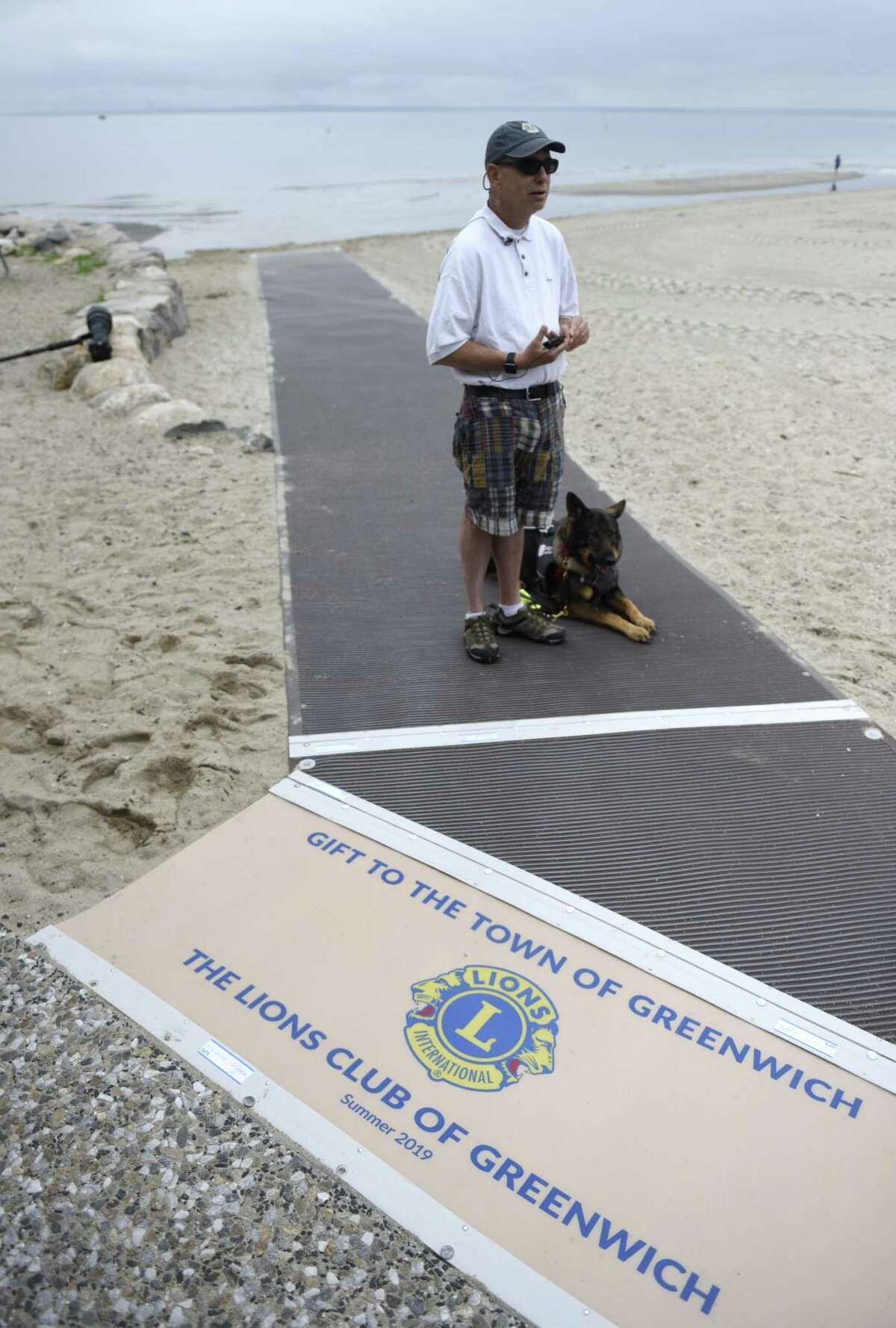 Alan Gunzburg, who serves on the First Selectman's Advisory Committee for People with Disabilities, stands on the new ADA accessible ramp on the Greenwich Point Park beach in Old Greenwich, Conn. Wednesday, June 19, 2019. The town held a ribbon-cutting for a new accessible beach mat that will make it far easier for people with disabilities to get to the beach.