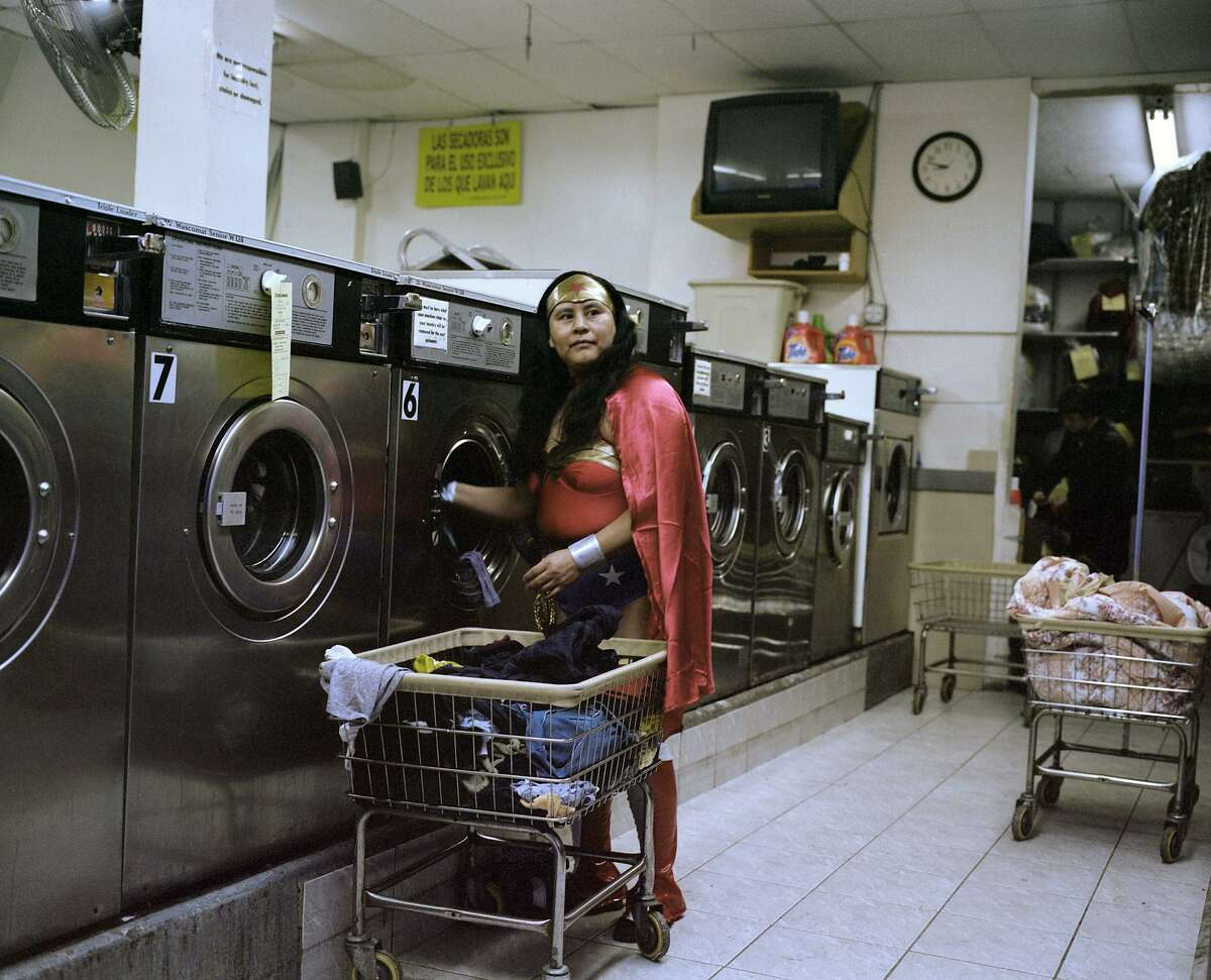 """Dulce Pinzon's photograph of Maria Luisa Romero, an immigrant from Puebla who works in a laundromat and sends $150 home to her family every week, is part of the """"Men of Steel, Women of Wonder"""" exhibit at the San Antonio Museum of Art."""