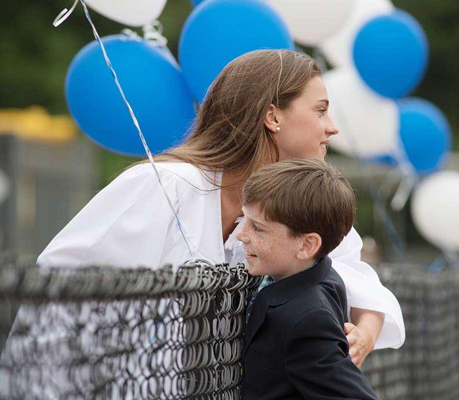 Senior Anna Stein hugged friend Ellen Ferguson's younger brother Andrew as Darien High graduates celebrated their 2017 commencement / BryanHaeffele