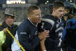 UConn coach Randy Edsall, center, leaves the field with quarterback Dan Orlovsky after the Huskies defeated Pittsburgh in a September 2004 game.