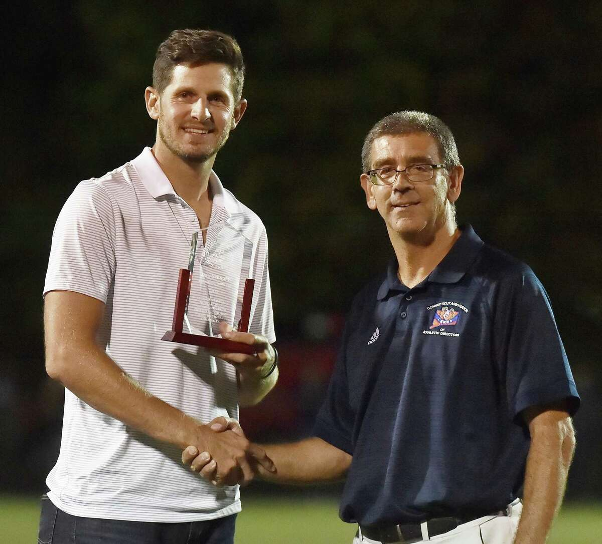 Shelton Athletic Director John Niskir, right, inducts former Gaels standout Dan Orlovsky into the Shelton High School Sports Hall of Fame on Oct. 6, 2017.