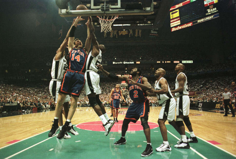 Chris Dudley, #14 of the New York Knicks, gets hammered as he goes to the basket by Tim Duncan, #21, and David Robinson, #50, of the San Antonio Spurs during Game 2 of the NBA Finals at the Alamodome in San Antonio. Photo: Matthew Stockman | Getty Images