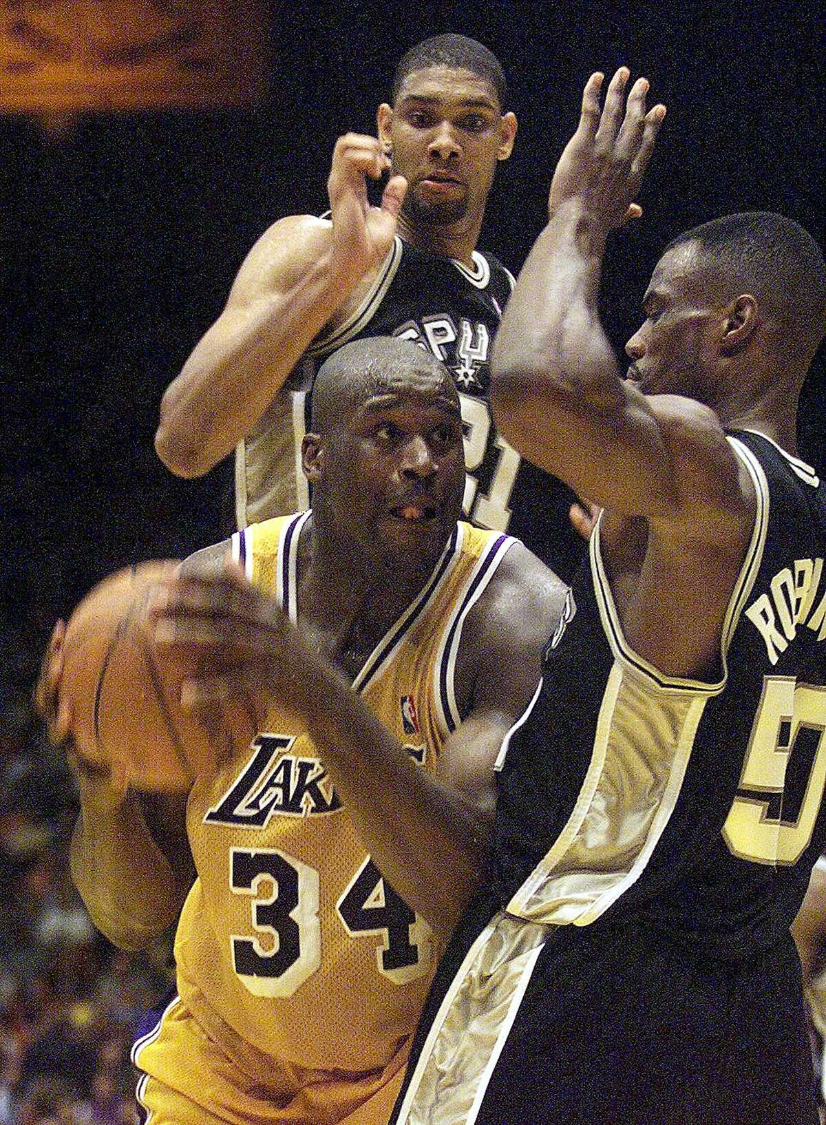 The Los Angeles Laker Shaquille O'Neal, center, goes up against the San Antonio Spurs' Tim Duncan, behind, and David Robinson during a Western Conference semifinals game in May of 1999. The Spurs defeated the Lakers 118-107 to advance to the Western Conference Finals.