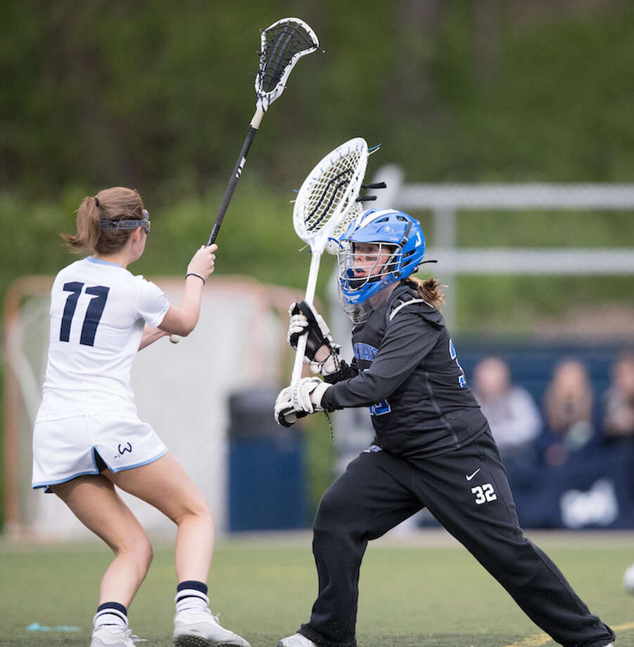 Carly Schoudel fends off a face full of pressure. Courtesy Darien Athletic Foundation / (c)Mark Maybell