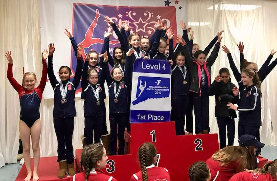 The Level 4 gymnasts celebrate their part of a Darien sweep of the team titles for every level they competed in at the Connecticut YMCA State Championships.