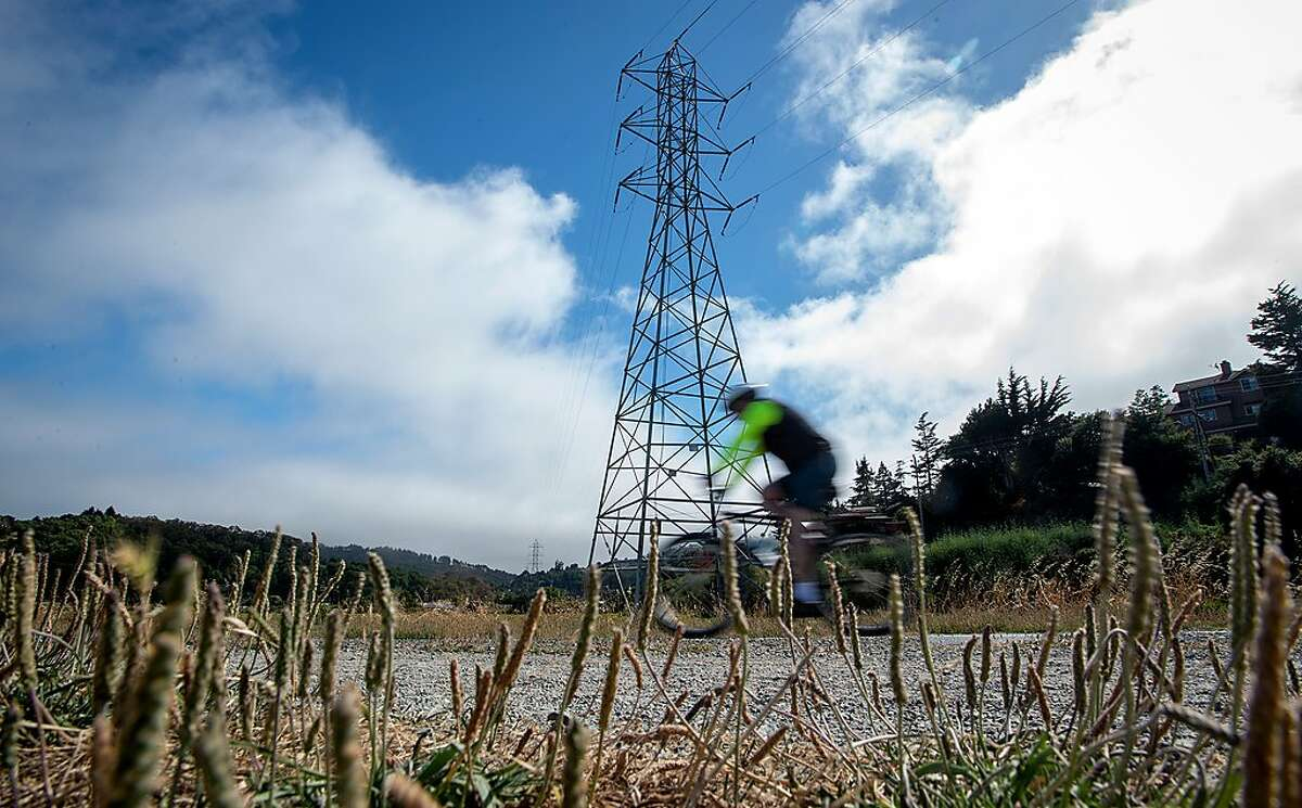 A bicyclist pedals by power lines in Mill Valley on Wednesday, June 19, 2019. PG&E is overhauling part of a major transmission line in Marin County that serves Sausalito.