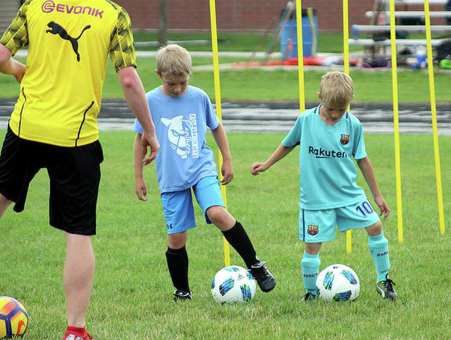 Campers Daniel Bruns, center, and Nathan Strong, right, dribble side by side under the watch of JCHS Panthers player Zane Longley during Wednesday evening's session of the JCHS Panthers Soccer Camp at Jersey Community High School.