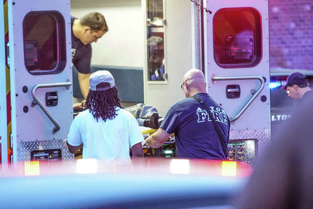 The victim of gunfire in Oakwood Estates Wednesday night is loaded into an ambulance.