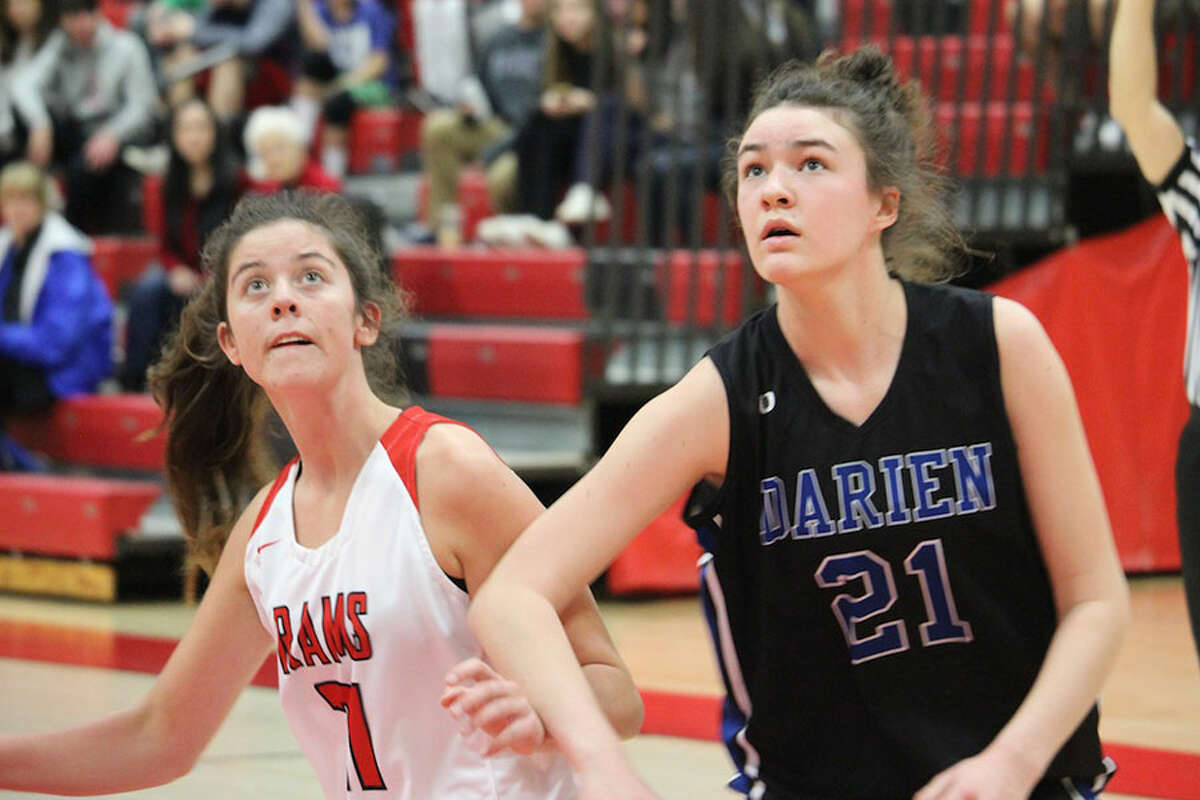 Darien's Aerin Bowman (21) and New Canaan's Quinn McKiernan battle for position during a free throw in Saturday's girls basketball game at NCHS. - Terry Dinan photo