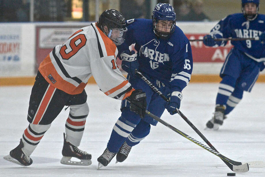 Darien's Sean Bradley (6) and Ridgefield's Braeden McSpedon (19) fight for the puck in the boys ice hockey game on Friday, Jan. 11 at the Winter Garden Ice Arena in Ridgefield. — H John Voorhees III/Hearst Connecticut Media photo / The News-Times