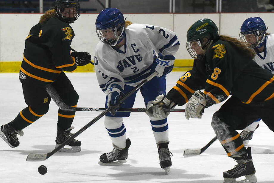 Darien's Colleen Cassidy (2) and Hamden's Claire Boncek battle for the puck during a girls ice hockey game at the Darien Ice House on Dec. 5.— Dave Stewart photo