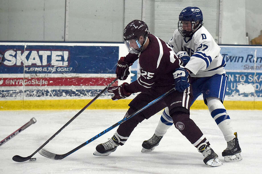 Darien's Nick Lancaster (27) battles La Salle's Kevin Kanaczet during Wednesday night's season-opener at Stamford Twin Rinks. — Dave Stewart photo