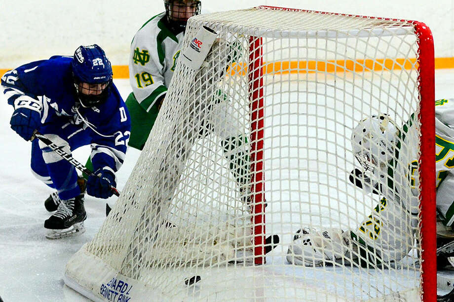 Darien's Bennett McDermott (22) slips the puck past Notre Dame of West Haven goalie David Anania to score during boys hockey action at Bennett Rink on Wednesday, Jan. 2. — Christian Abraham/Hearst Connecticut Media photo / Connecticut Post