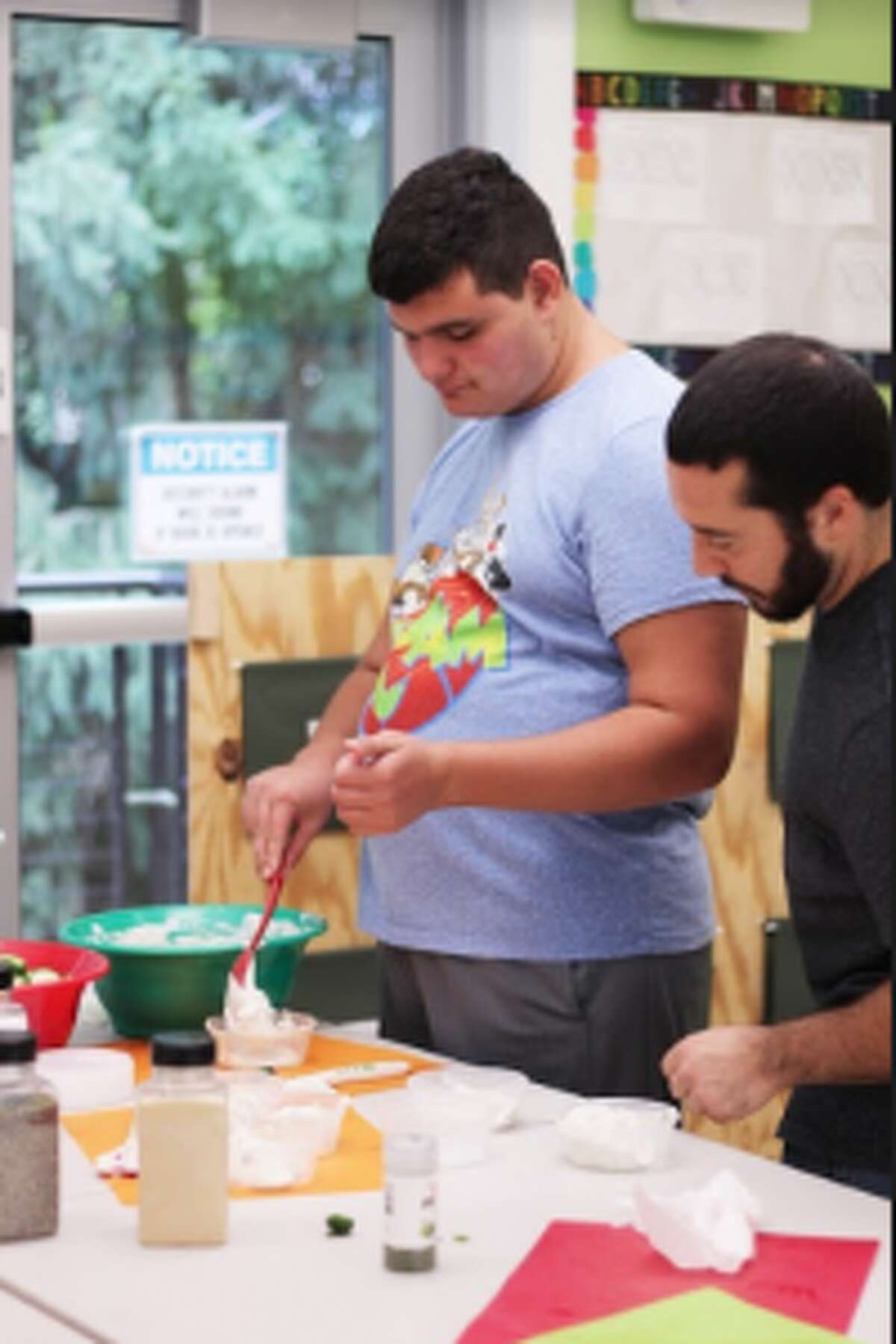 Jon Carlo Kearney, 19, gets assistance from Darien YMCA staff member Noel Senna in preparing snacks, as part of the Innovative Vocations program.