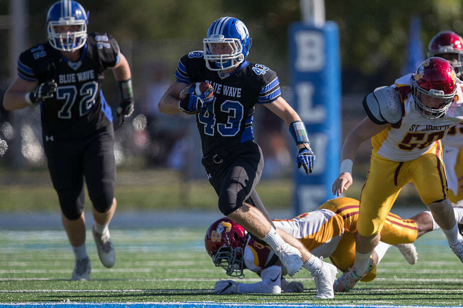 Running back Andrew Lucas races for a big gain during Darien's victory over St. Joseph last fall. Lucas and Will Kirby lead the Blue Wave's rushing attack this season. — Darien Athletic Foundation photo / (c)Mark Maybell
