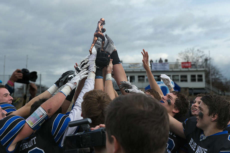 The 2015 Darien Blue Wave hoist the Coaches Memorial Trophy, awarded to the winner of the Turkey Bowl each season. —Dave Stewart photo