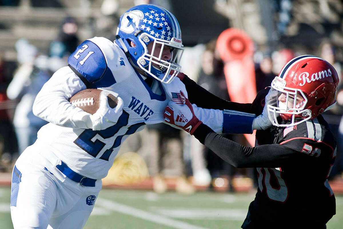 Darien's Will Kirby goes head-to-head with New Canaan's Dean Ciancio during the Turkey Bowl football game Thursday at Boyle Stadium in Stamford. - Scott Mullin photo