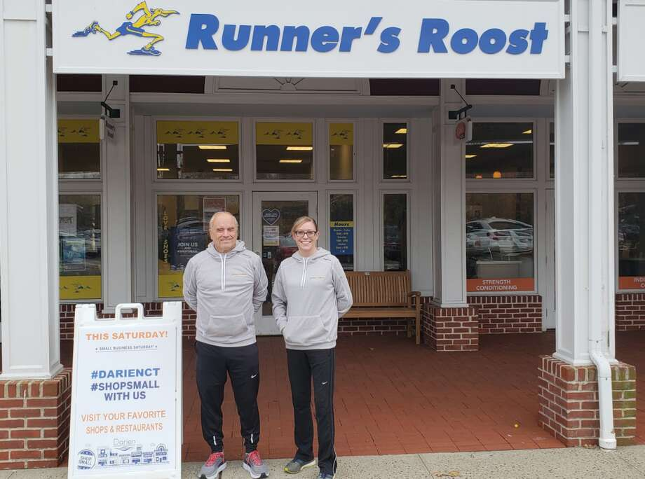 Owner Steve Norris with media manager Emily Kane in front of Runner's Roost in Darien.
