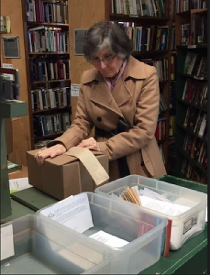 Volunteer Frances Cavosa selects titles and packing boxes of books for shipment. The books are sent through Darien Book Aid Plan, a nonprofit organization that provides free books to people in need around the world.