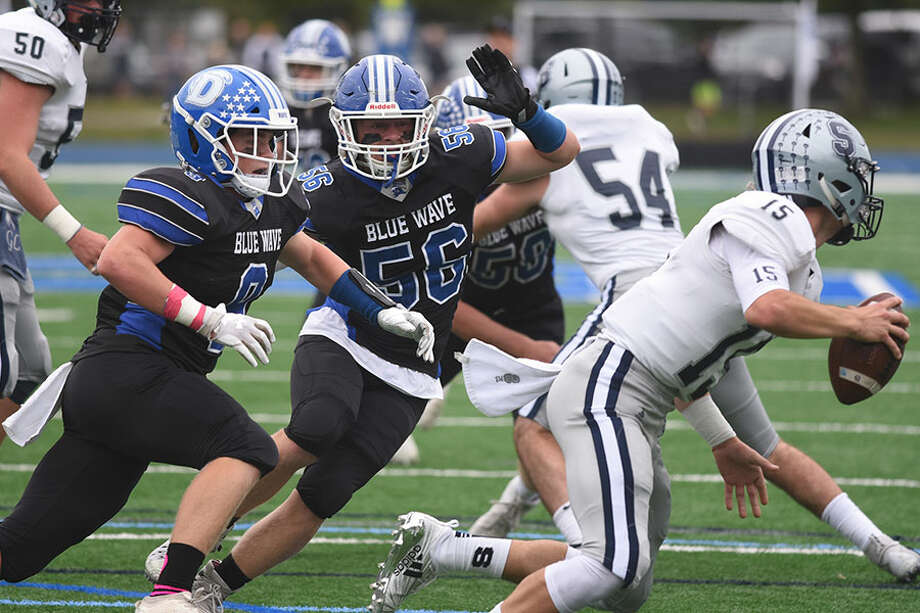 Darien's John Lochtefeld (56) and Sam Wilson (9) chase down Staples quarterback Jake Thaw during the Blue Wave's 24-0 win on Oct. 6 at DHS. — Dave Stewart photo