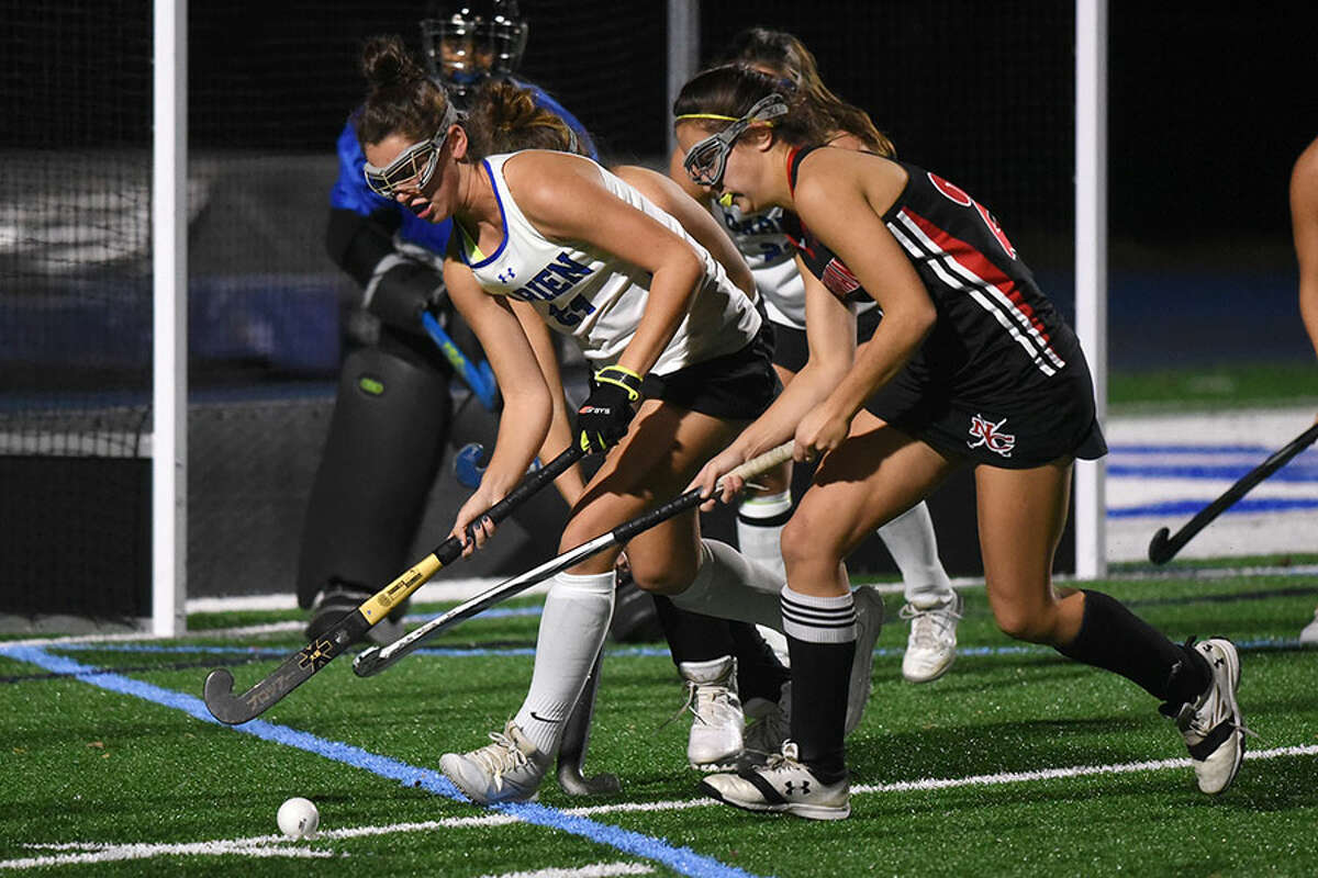Darien's Lindsey Olson, left, and New Canaan's Marlee Smith battle for possession during a Class L field hockey playoff game on Wednesday in Darien. - Dave Stewart photo