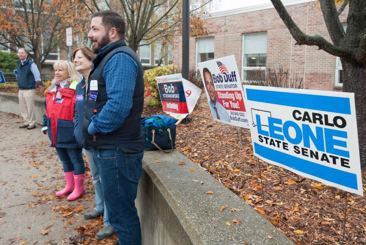 Selectman Susan Marks, Republican Town Committee member Belinda Metzger and RTC Chairman Chris Taylor greeted voters outside Town Hall.