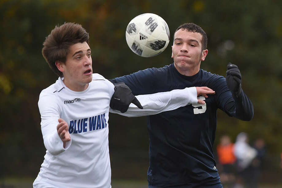 Darien's Cole Branca and Staples' Eleftherios Pendarakis battle for the ball during the first round of the Class LL boys soccer playoffs Tuesday in Westport. — Dave Stewart photo