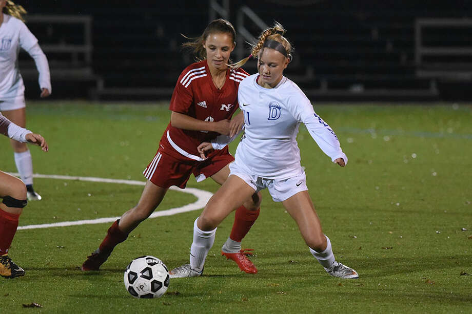 Darien's Lauren Sulger (11) and New Canaan's Sophie Potter battle for the ball during the FCIAC girls soccer semifinals Monday night at Wilton High School. — Dave Stewart photo