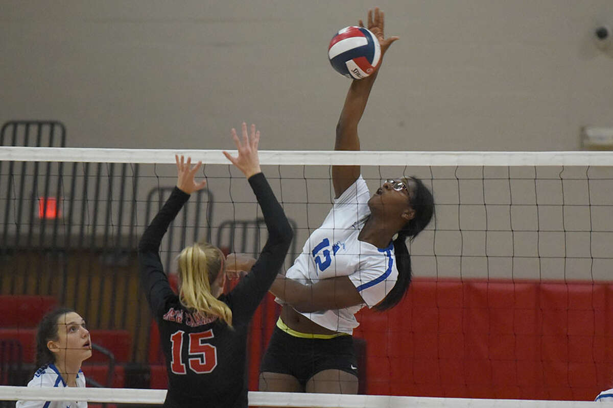 Darien's Hassana Arbubakrr puts down a shot during the Wave's 3-0 win over the rival Rams in New Canaan on Monday. - Dave Stewart photo