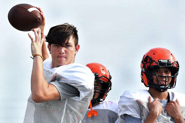 Edwardsville junior quarterback Ryan Hampton warms up on the sideline during a summer workout session at the District 7 Sports Complex in Edwardsville.