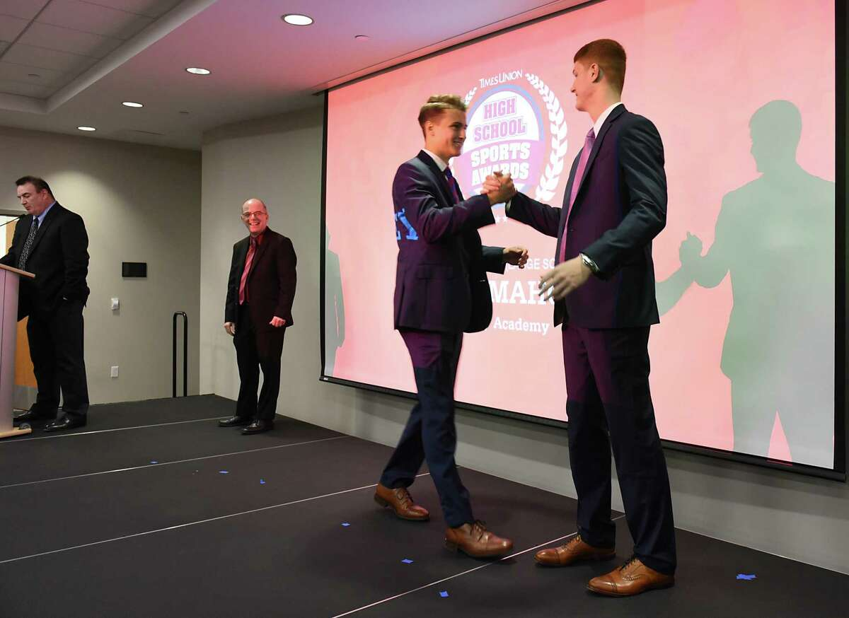 Albany Academy's August Mahoney shakes hands with local NBA star Kevin Huerter, right, after he received the boys basketball large school award during the second annual High School Sports Awards show at the Hearst Media Center on Wednesday, June 19, 2019 in Albany, N.Y. (Lori Van Buren/Times Union)