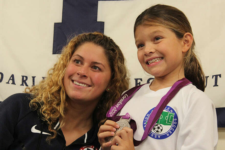 Olympic swimmer Elizabeth Beisel posing with the Piranhas' Tessa Michaelis while holding one of her Olympic medals — Pawel Frankowski/Franzvideo Photo