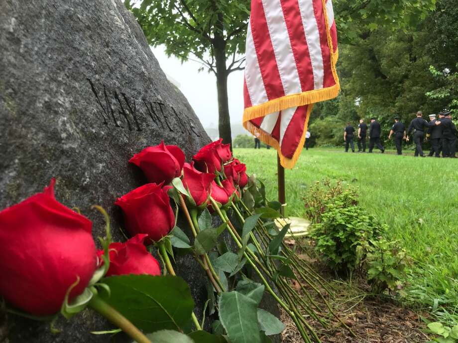 Darien first responders leave the 9/11 memorial Tuesday morning after the town's ceremony. Many attendees left roses of remembrance. — Susan Shultz photo