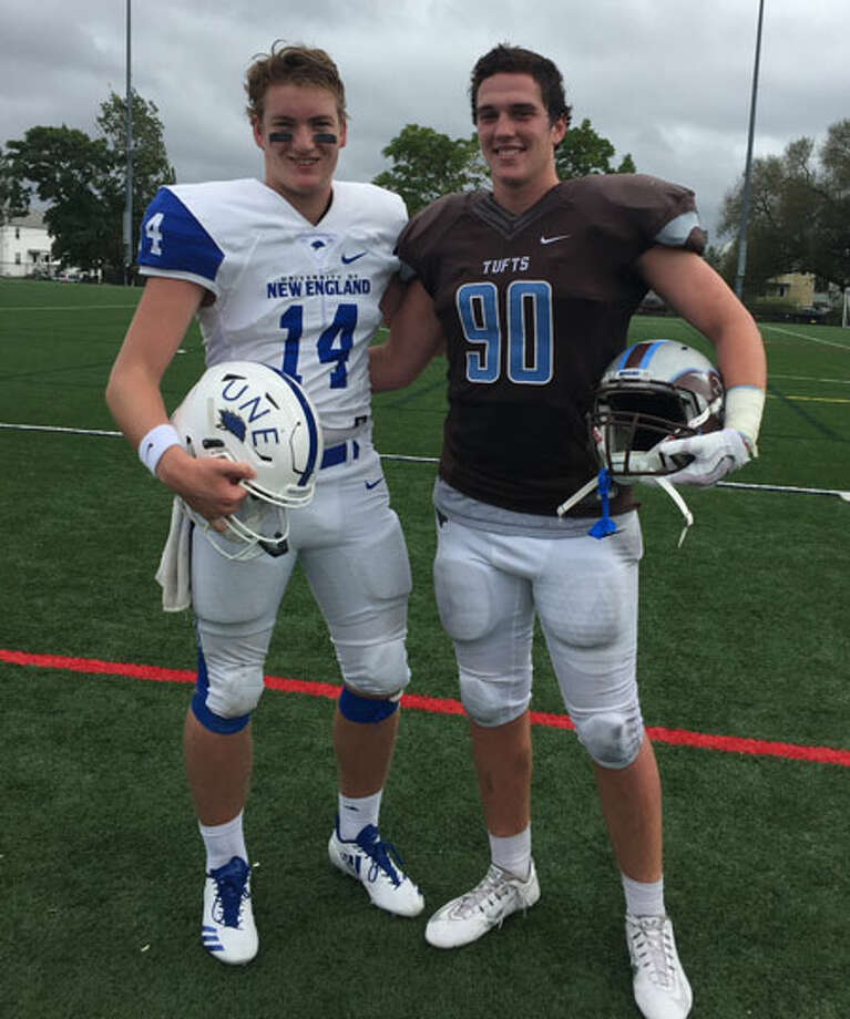 Former Darien teammates Brian Peters (14, left) of the University of New England and Quinn Fay (90) of Tufts University meet on the field during a football game last fall.