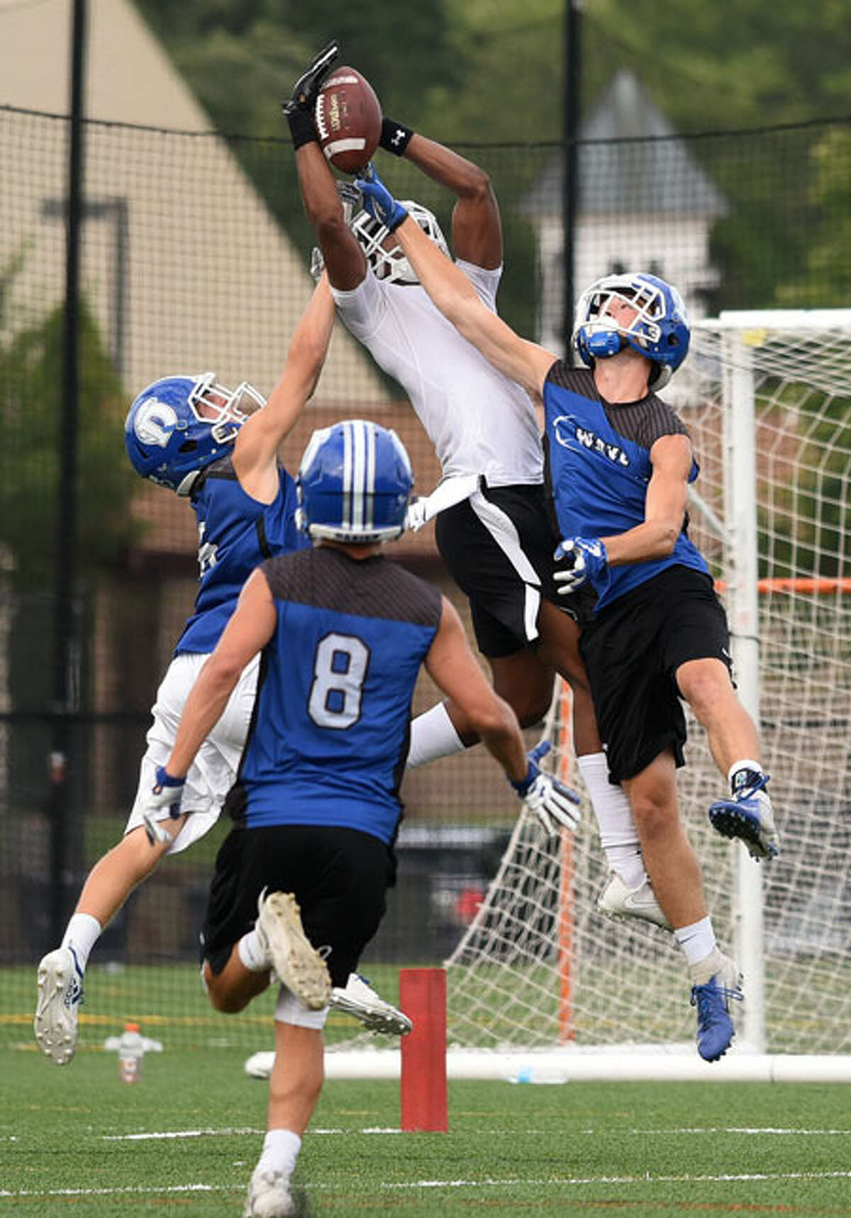 The Darien defense was in fine form as a possible touchdown pass is tipped away from a Brunswick receiver by the Blue Wave's Tyler Herget during the annual Grip It and Rip It 7-on-7 passing tournament in New Canaan last weekend. - Dave Stewart photo
