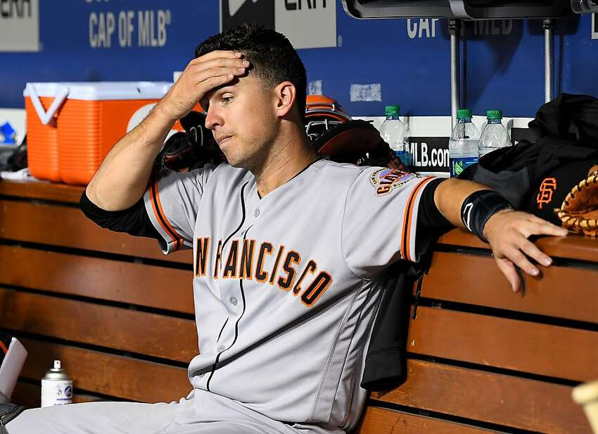 Buster Posey #28 of the San Francisco Giants sits in the dugout in the fifth inning of the game against the Los Angeles Dodgers at Dodger Stadium on June 19, 2019 in Los Angeles.