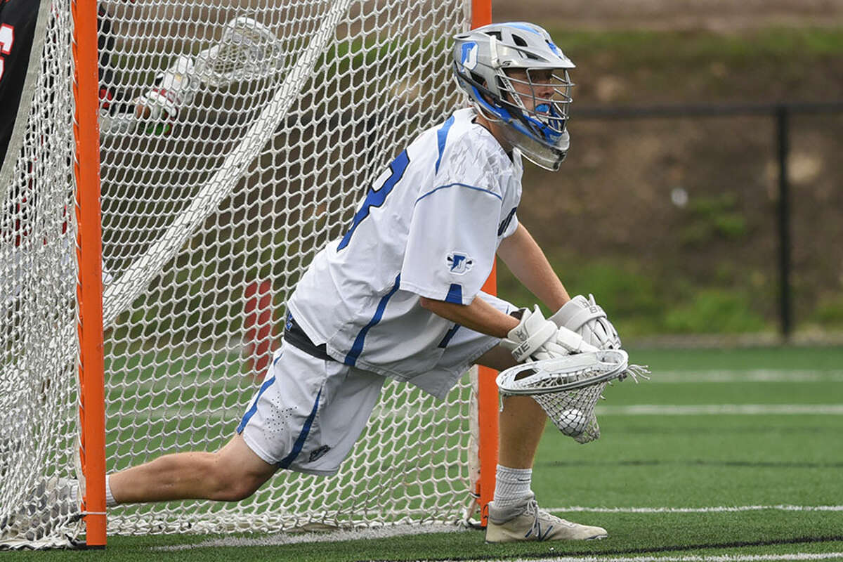 Sean Collins looks to clear after making one of his 12 saves in the Class L semifinals against New Canaan. - Dave Stewart photo