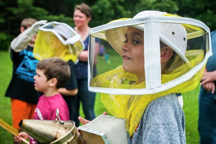 (Above) Owen Finney of Sanford, 13, wears a beekeeping veil during an event called 'Meet the Bees' at Chippewa Nature Center on Wednesday afternoon. For more photos, go to www.ourmidland.com. (Right) Cathy Fitzpatrick, a historical interpreter with Chippewa Nature Center, shows guests two beehives during an event called 'Meet the Bees' at Chippewa Nature Center on Wednesday afternoon. (Katy Kildee/kkildee@mdn.net)