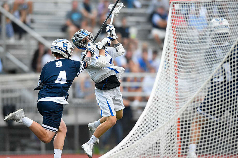 Staples' Jack Dorsey defends as Darien's Michael Minicus fires a shot on Staples goalie Tim Luciano (91) in a CIAC boys lacrosse Class L state tournament semifinal game at Brien McMahon High School on Wednesday night. — Matthew Brown/Hearst Connecticut Media / Stamford Advocate