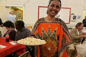 An Eritrean refugee shows the meal she has prepared through Ciri's Ethnic Eats program. – Sandra Diamond Fox photo